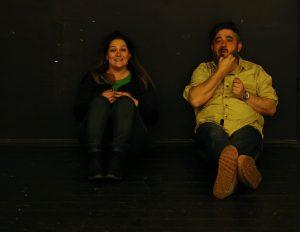 Nő és férfi földön ülnek egymás mellett, hátukat a falnak támasztva. Figyelnek valamire.