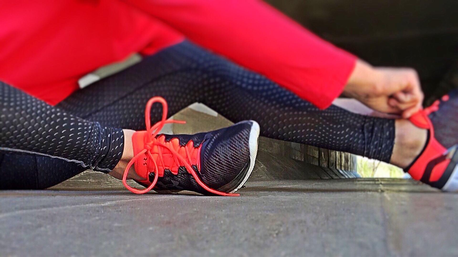 Női piros edzőcipőt húz a lábára