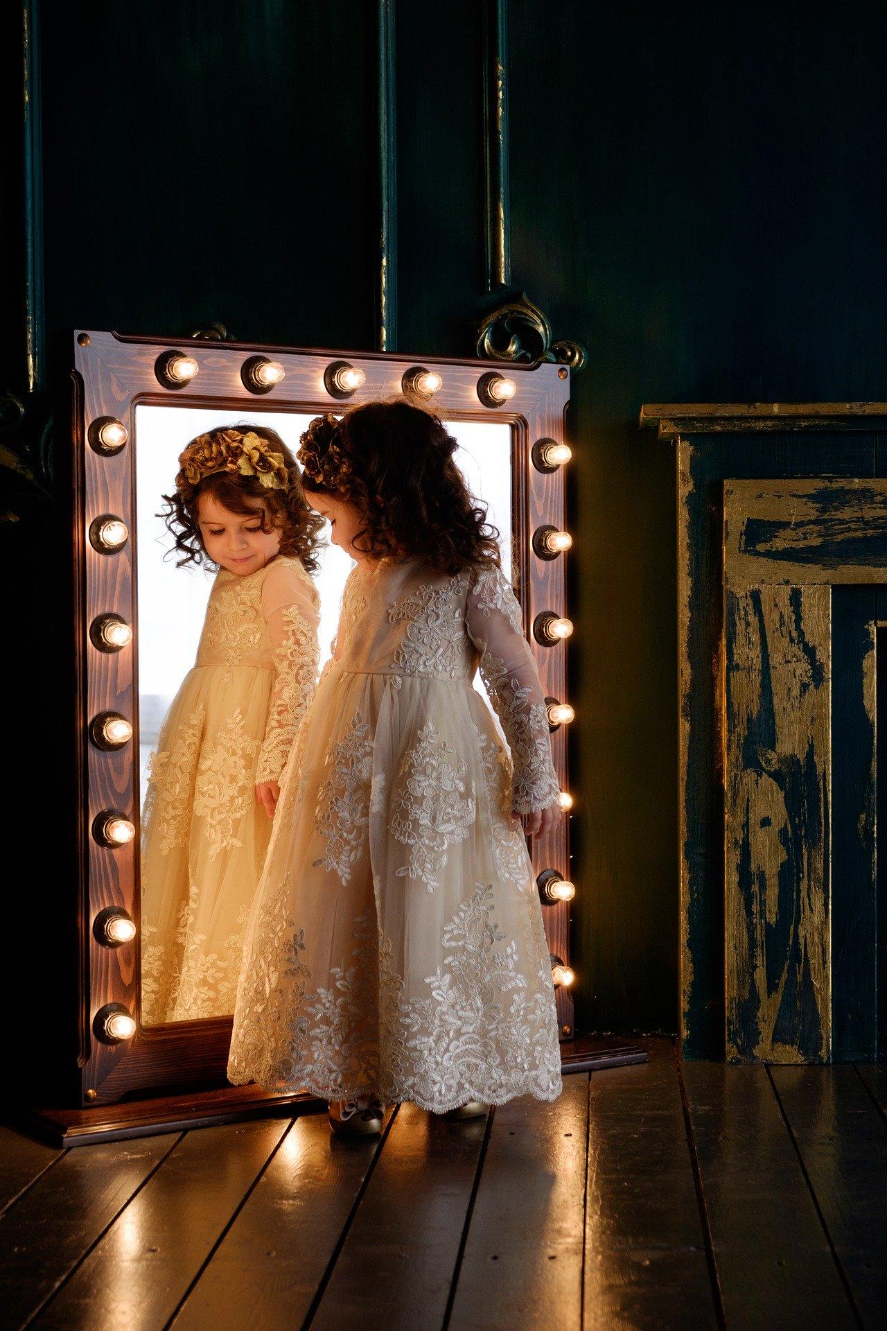 Kislány áll a tükör előtt